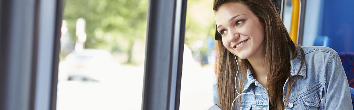 Teenage Girl Wearing Earphones Listening To Music On Bus
